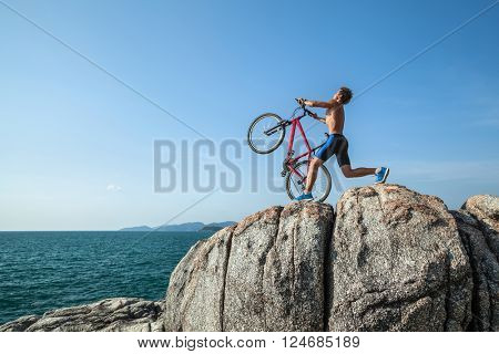 Half-naked sportman carrying a bicycle on the rock