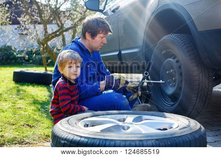 Cute blond kid boy and his father changing wheels on car with pneumatic wrench. Man in uniform teaching his son working with tools.