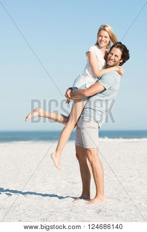 Portrait of happy young man picking up his girlfriend. Couple at beach enjoying on a sunny day. Happy young couple smiling at seaside.