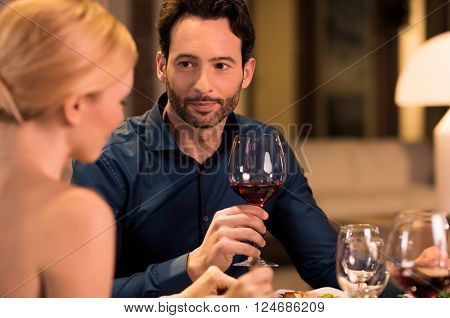 Happy young couple in a restaurant for dinner. Young handsome man looking at his girlfriend with love. Man listening to talk his girlfriend during dinner in a luxury restaurant.