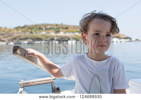 Cute boy with hand on rudder looking away