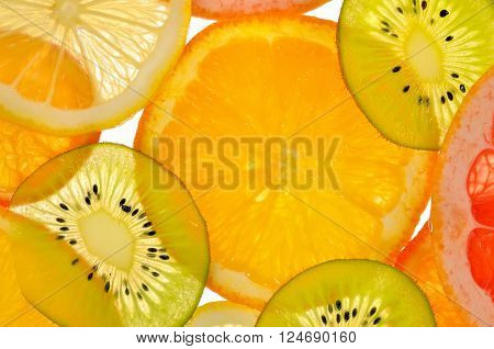 Different sliced juicy citrus fruits, abstact background