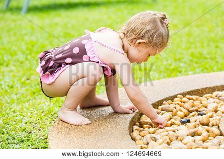 Cute little child girl in a swimsuit playing with stones on a pebble beach
