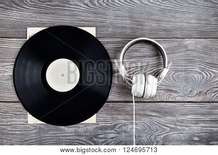 Vinyl record and headphones on wooden background
