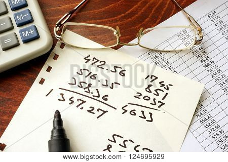 Business calculation concept. Papers with data and calculator.