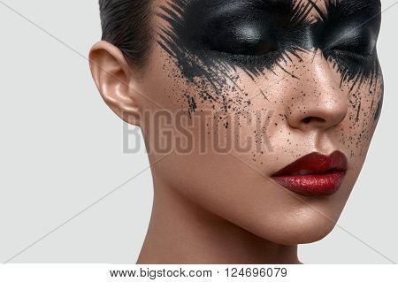 Beauty female Model with closed eyes and black Paint Stains on her Face. Creative Face Art for Magazine or Poster