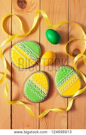 Easter homemade gingerbread cookie and yellow end green eggs with ribbon over wooden table. Colorful toned image top view