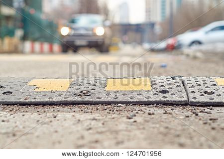 Speed Bump closeup with a car approaching on the background