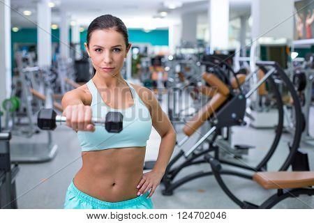 Photo of beautiful young sporty woman. Fitness girl training woth dumbbell in sport club with exercise equipments. Woman looking at camera. Focus on dumbbell