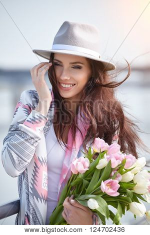 Young woman with a bouquet of tulips at the street.
