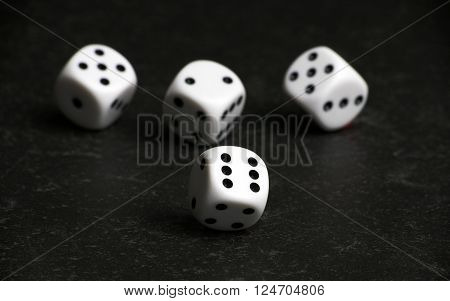 Four white and black dice on a black table