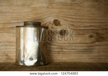 paint bucket or paint can on wooden background, artist using paint bucket for mixing color for pictures.