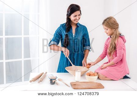 Sweet time of family cooking. Mother and daughter having fun while preparing meal. Nice white interior. Daughter helping with eggs