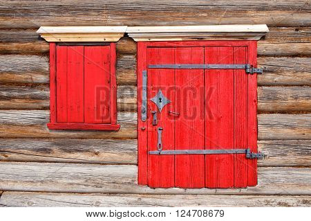 wooden door and window with shutters. log wall an ancient house with a red door and window