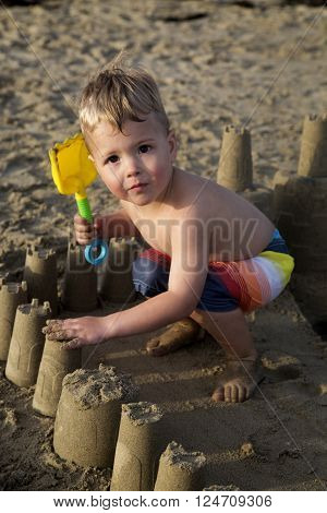 Brown eyed blond boy playing in sandcastle ** Note: Soft Focus at 100%, best at smaller sizes