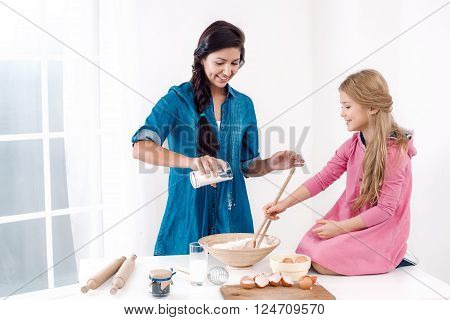 Sweet time of family cooking. Mother and daughter having fun while preparing meal. Nice white interior. Mother pouring flour in dough