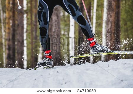 Kyshtym Russia - March 26 2016: feet men skier sprays snow from under ski during Championship on cross country skiing