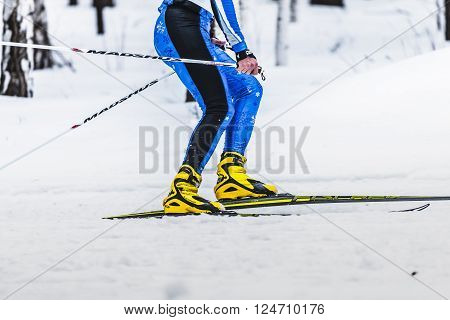 Kyshtym Russia - March 26 2016: skiers male athletes running on track side view during Championship on cross country skiing