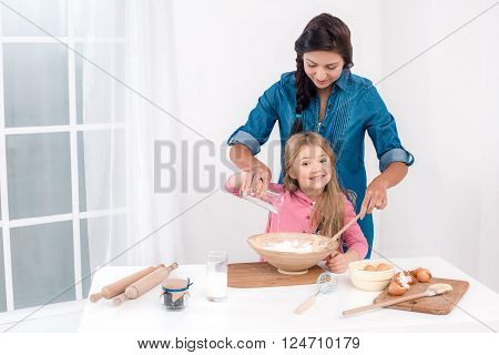 Sweet time of family cooking. Mother and daughter having fun while preparing meal. Nice white interior. Daughter and her mom kneading the dough