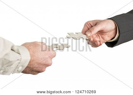 Two hands coming from opposite directions matching two puzzle pieces. Isolated over white background.