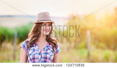 Close up of beautiful young gardener in checked shirt and hat, in green sunny nature