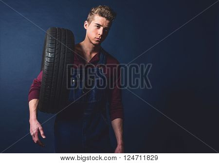 Vintage 1950S Mechanic In Jeans Bib And Brace Holding Tire.