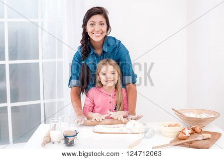 Sweet time of family cooking. Mother and daughter having fun while preparing meal. Nice white interior. Mother and daughter kneading the dough