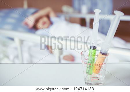 Syringes In A Glass Measuring Cup With Blurred Illness Boy Lying On Sickbed. Vintage Style.