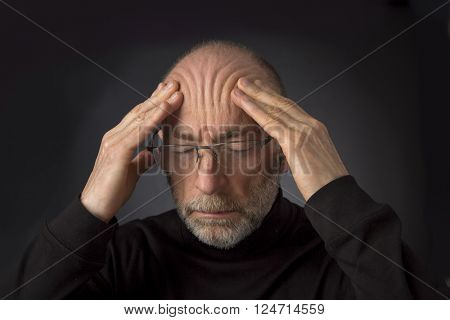 tired - 60 years old  man with a beard and glasses massaging his forehead -  a headshot against a black background