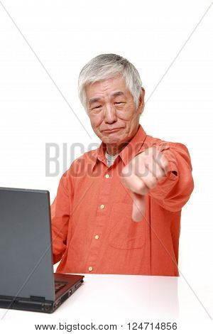 senior Japanese man using computer looking confused