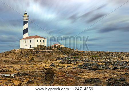 Cap de Favaritx lighthouse, Menorca landmark and eroded landscape an overcast day