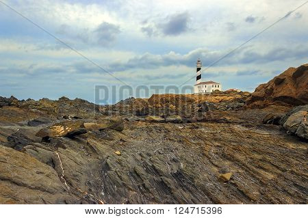 Cap de Favaritx eroded rocks, landscape with weathered ground and a lighthouse on background, Menorca, Spain
