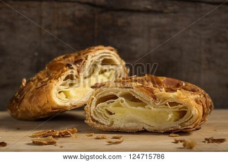 Section of one strudel with almonds and vanilla ice cream over rustic wooden background