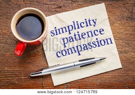 simplicity, patience, compassion - three words from Buddha teaching - handwriting on a napkin with cup of coffee against gray slate stone background