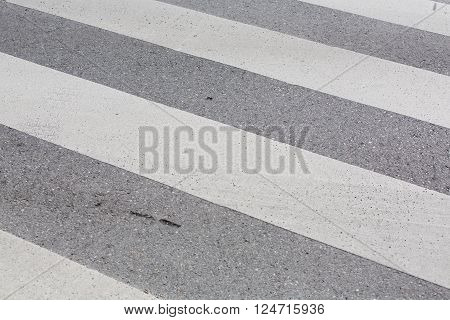 zebra crossing on a concrete road with white stripes.