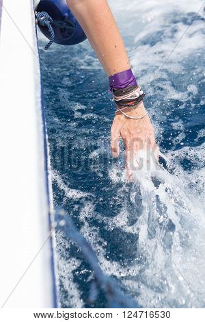 Unrecognizable woman touching splashes of foaming water while floating on yacht