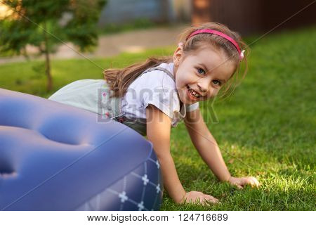 Portrait of a beautiful little girl smiling at the camera while playing on grass outside
