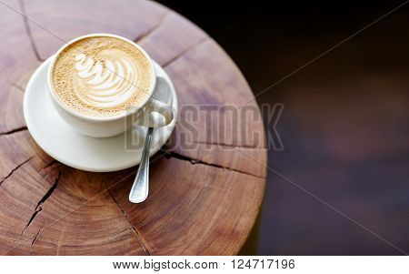 Closeup of a cappucino on a wooden stump with beautiful natural patterns