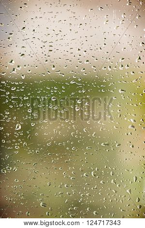 Water drops on a window with outdoor background