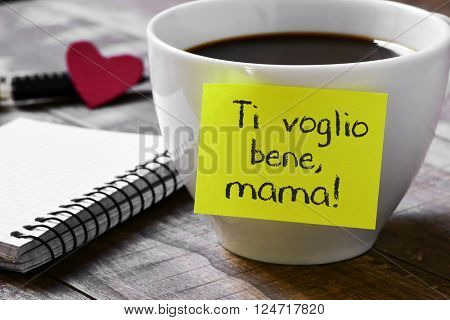the sentence ti voglio benne mama, I love you mom written in italian in a yellow sticky note placed in a cup of coffee, on a wooden table next to a notepad and a red heart in the background