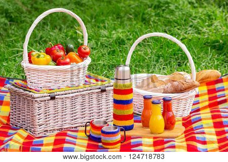 Picnic on the grass. Picnic basket with vegetables and bread. A thermos of tea and bottles of juice.