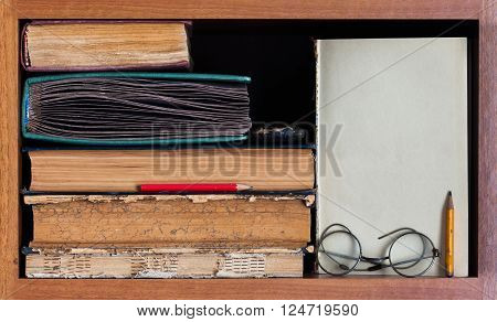 Still life with wooden book shelf, rare antique books, textured pages, pencils, blank paper scroll and retro design glasses. Path to wisdom concept