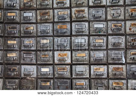 Antique filing system. Retro design metal boxes with aged paper nameplates. Old time storage cabinet. Information management and security concept image. Textured, shabby, dirty silver texture
