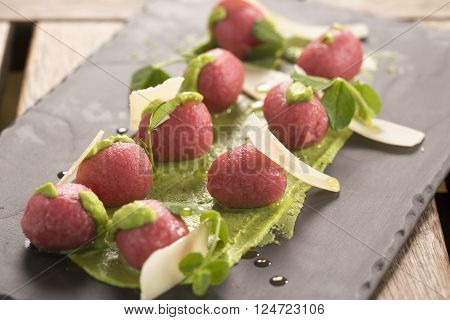 Beetroot & goats cheese gnocchi with pea puree, shaved pecorino, micro basil & olive oil