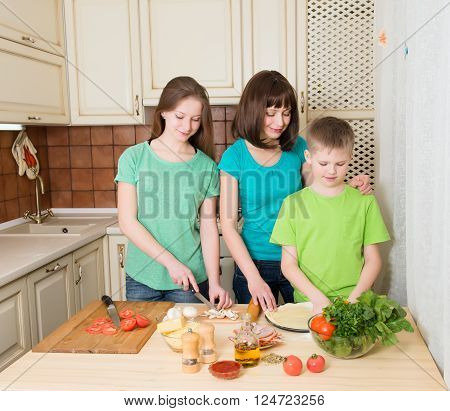 Teenager boy and girl with their mother cooking pizza at home. Portrait of mom with her helping kids making pizza in the kitchen.