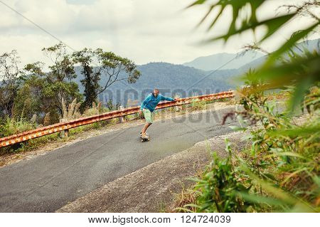 hipster man longboarding extremely in tropical vacation