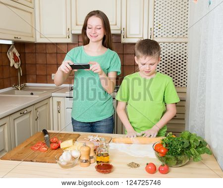 Children cooking homemade pizza at home kitchen. Smiling girl taking food photo with smartphone.