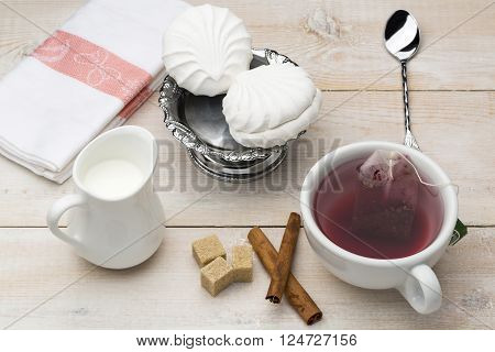 Set of cup red tea and dessert on bright wooden table