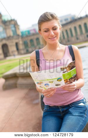 Female tourist reading a travel guide to the Zwinger palace, Dresden, Germany