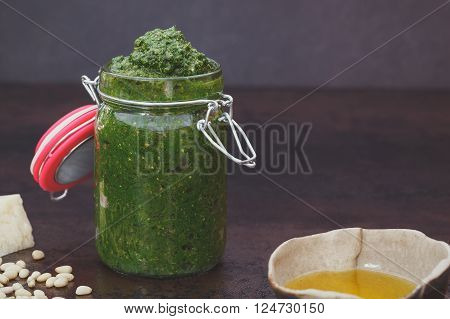 Homemade pesto. Homemade pesto  in a jar and ingredients on dark background. Macro, selective focus, vintage toned image, blank space